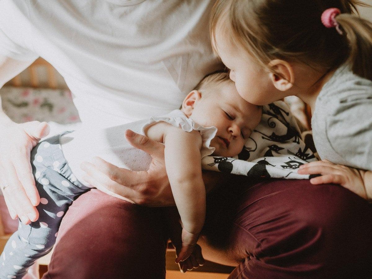 little girl kissing her little sister
