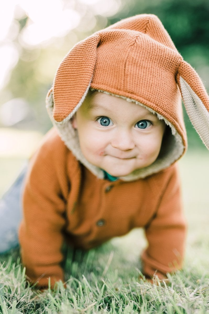 Little toddler in bunny rabbit suite on the grass during a photography session in the park