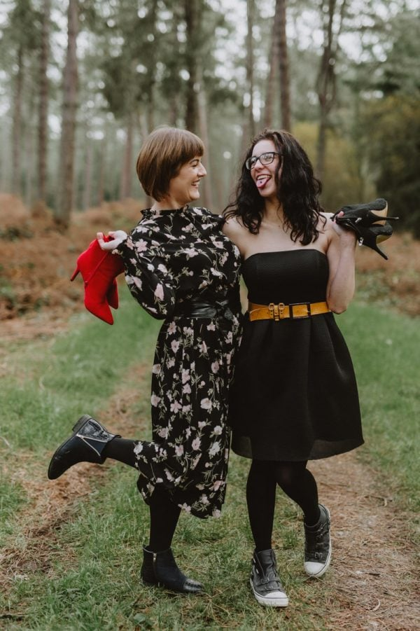 mum and her teenage daughter standing in the forest happ holding their shoes in the hands