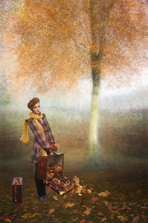 fine art photo of a girl with suitcase full of autumn leaves under the tree