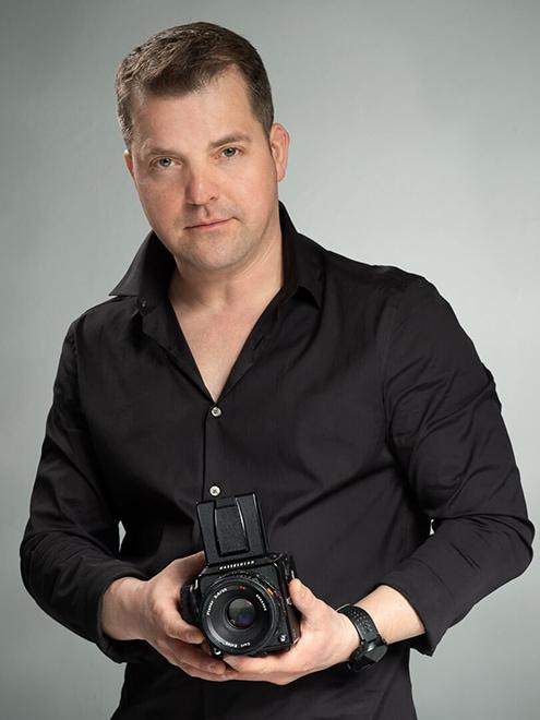 studio portrait of a man holding camera