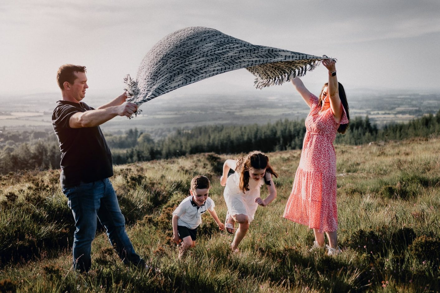 family plays with their kids on the top of the mountain
